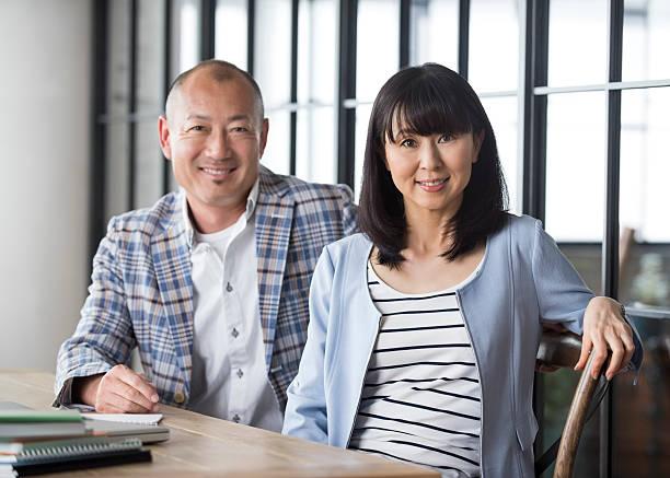 japanese couple sitting at table - mid volwassen koppel stockfoto's en -beelden