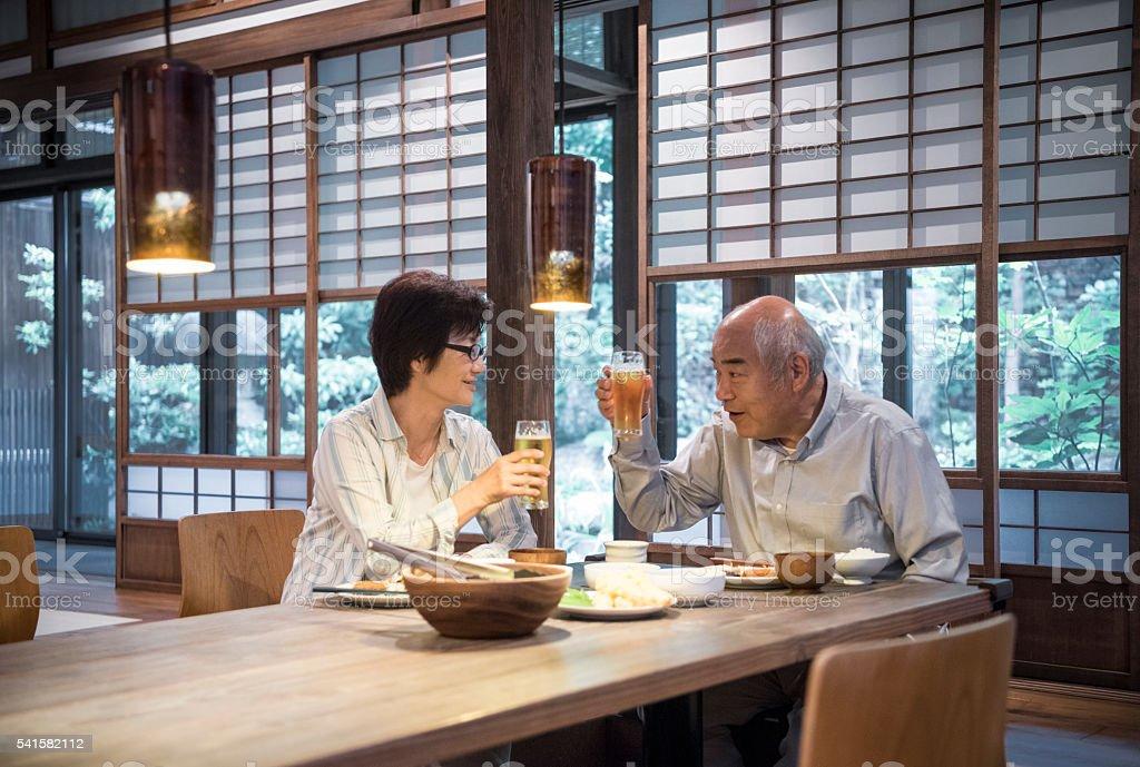 日本人夫婦で乾杯するビールグラス、夕食 ストックフォト