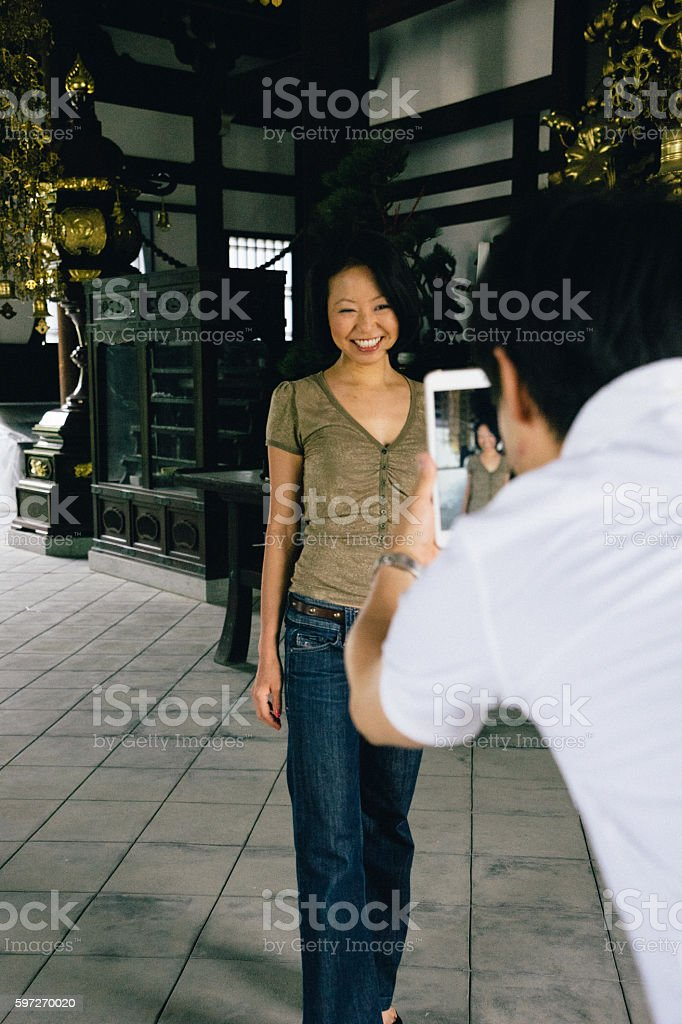 Japanese couple visiting a buddhist temple taking a memory picture royalty-free stock photo