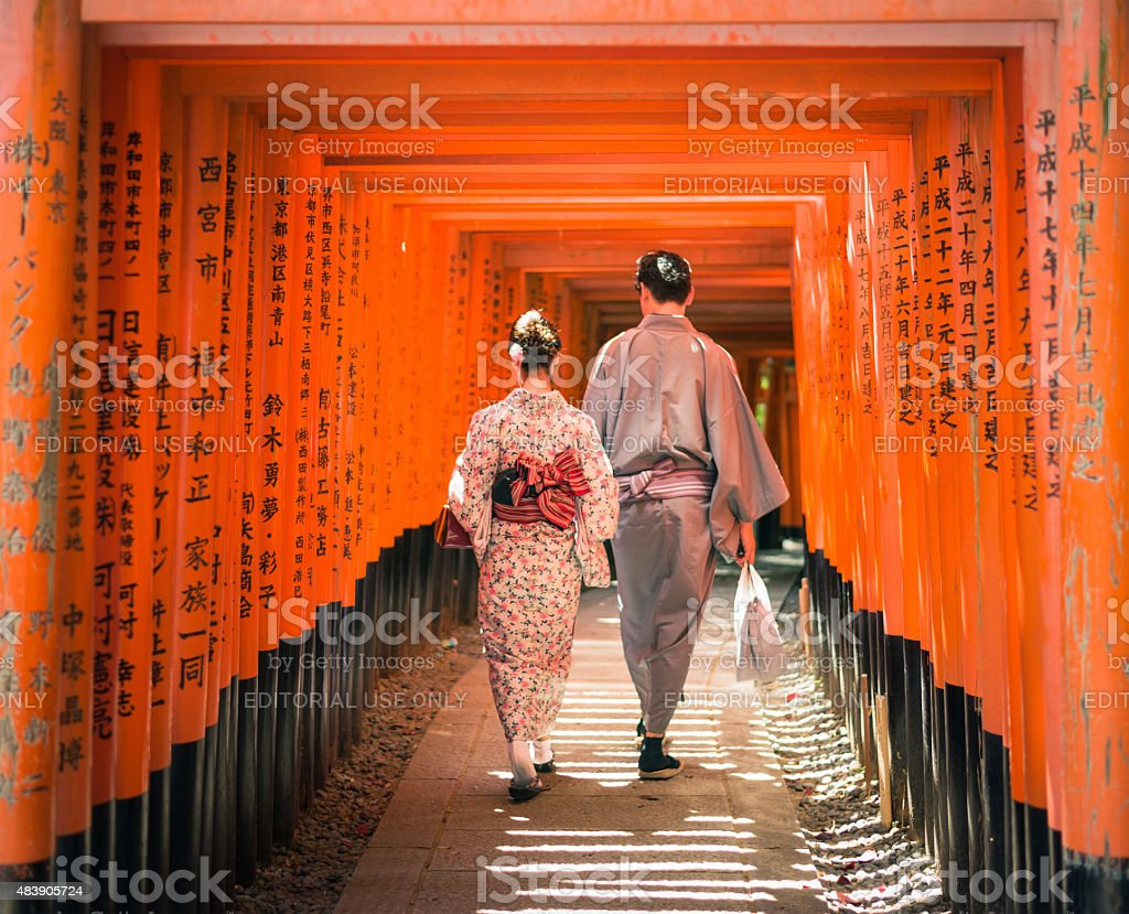Japanese couple walking through Torii gates at Fushimi Inari-Taisha stock photo