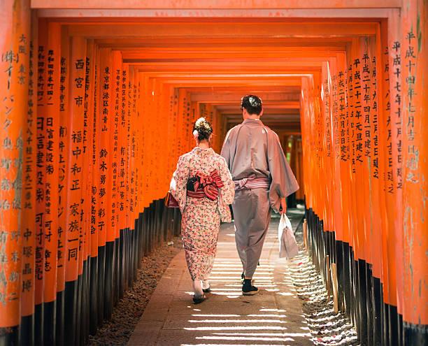 Japanese couple walking through Torii gates at Fushimi Inari-Taisha Kyoto, Japan - May 11, 2015: A couple wearing traditional Japanese kimonos, walking through a long series of inscribed Torii gates at Fushimi Inari-Taisha, on the outskirts of the ancient Japanese city of Kyoto. torii gate stock pictures, royalty-free photos & images