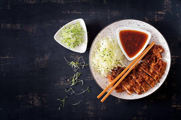 japanse keuken. gefrituurde karbonade of japanse chop met kool en tonkatsu saus. bovenaanzicht - japanse gerechten stockfoto's en -beelden
