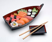 Japanese food, sushi assortment on the decorative plate ship, and soy sauce, and chopsticks.