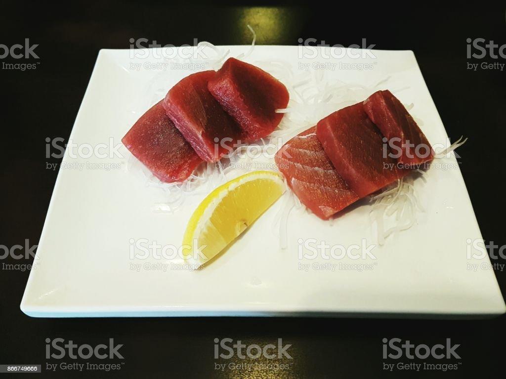 Japanese cuisine -  slices of  fresh tuna sashimi / maguro served on white plate.