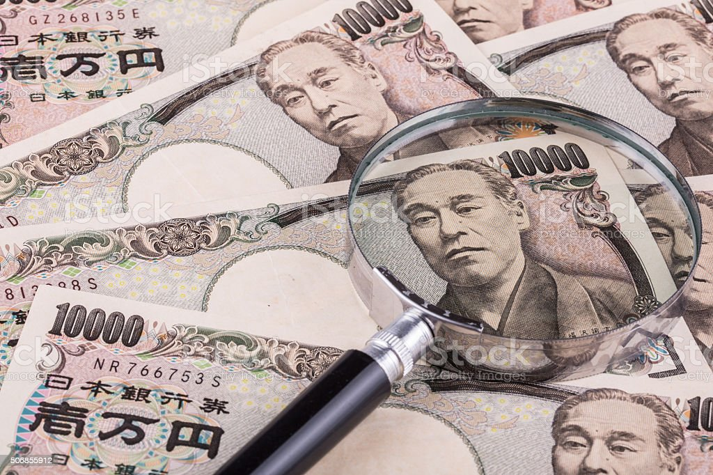 Japanese currecny 10000 yen with magnifying glass stock photo