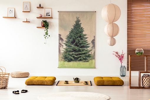 istock Japanese dining room interior with a tree poster, lamp, pillows and tatami mat with pot and cups on the floor 971380606