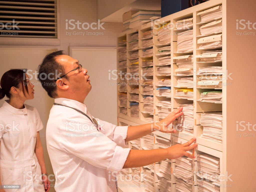 Japanese doctor checking patient's clinical record stock photo