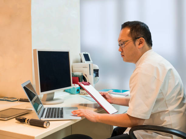 Japanese doctor checking patiient data from PC. stock photo