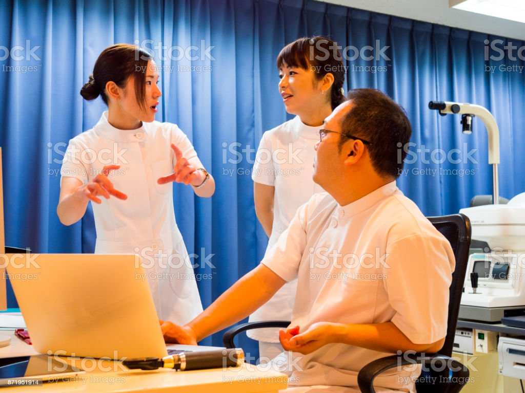 Japanese doctor checking the patient data with nurses. stock photo