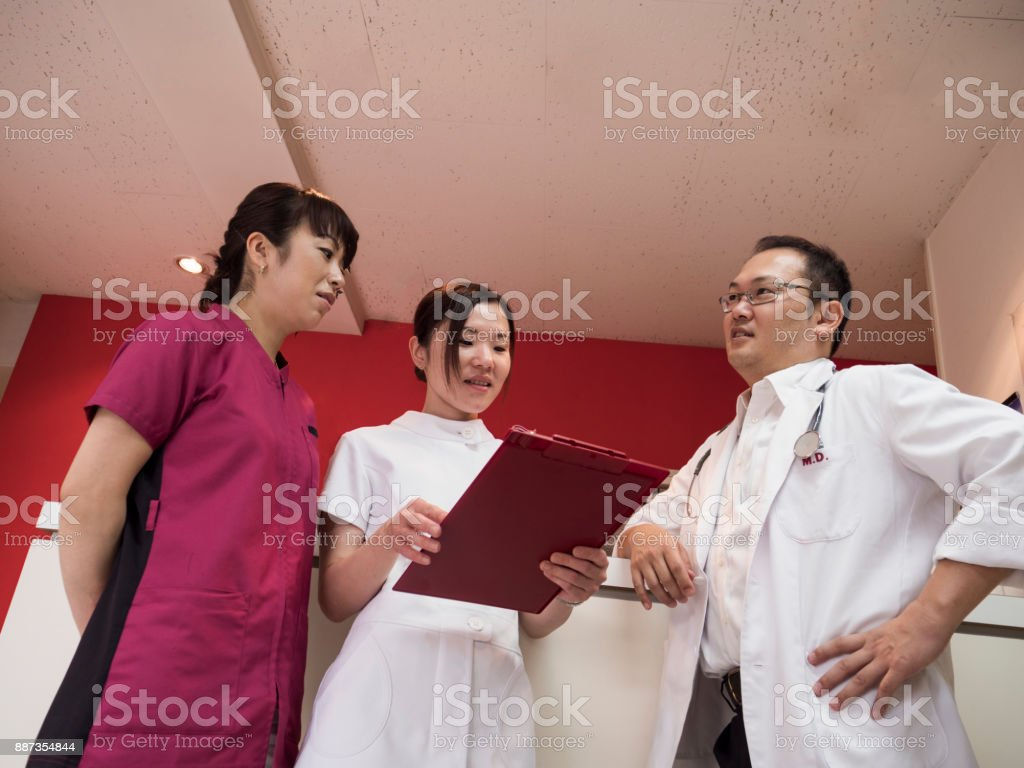 Japanese doctor discussing with nurses. stock photo