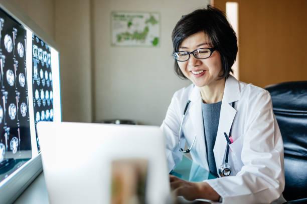 Japanischer Arzt mit Computer und Blick auf Röntgenstrahlen – Foto