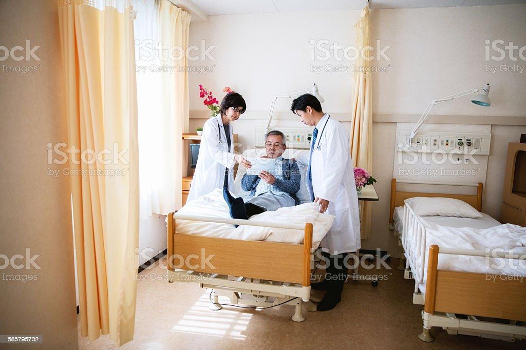 Japanische Arzt im Gespräch mit einem Patienten im Krankenhaus – Foto