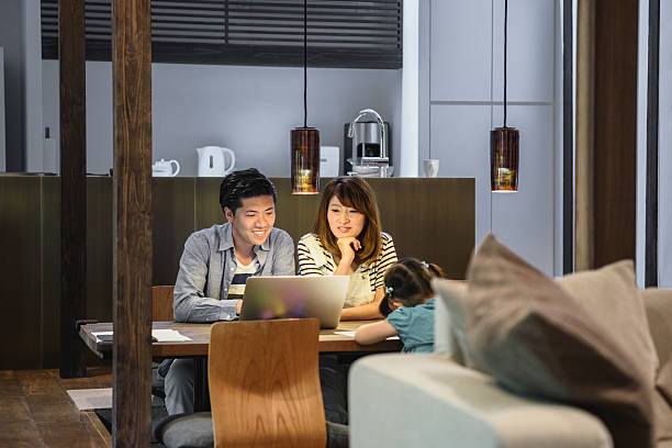 japanese family at home, parents watching laptop - 両親 ストックフォトと画像