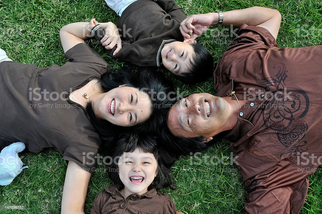 Japanese family laying on the grass with heads together royalty-free stock photo