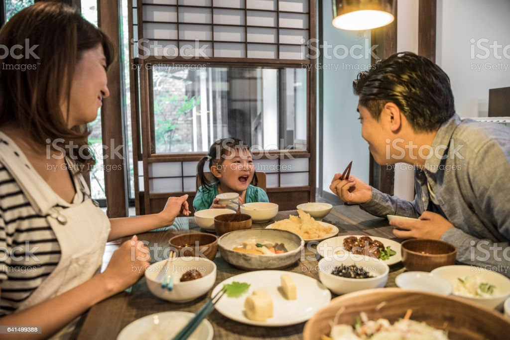 Japanese family sitting at dining table eating dinner stock photo