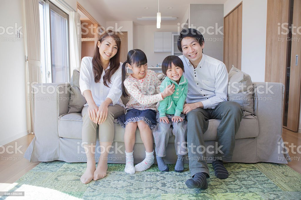 Japanese family sitting on sofa stock photo