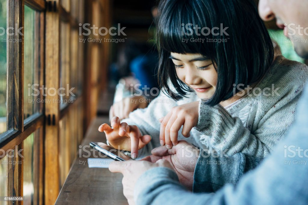 Japanese family using smartphone together stock photo