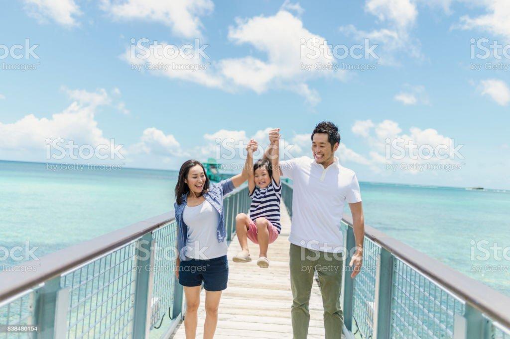 笑顔で桟橋を歩く日本の家族サンバシアル ストックフォト