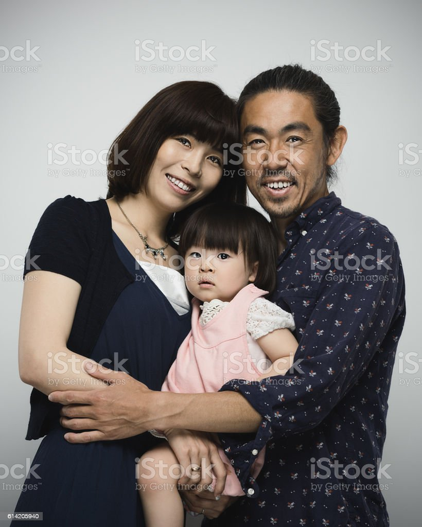 Japanese family with parents embracing the baby daughter stock photo