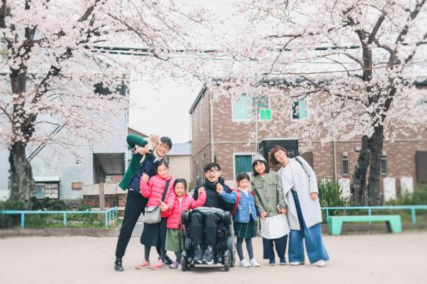 Japanese family with wheelchair man in spring 2 japanese family enjoy the weekend at the park amyotrophic lateral sclerosis stock pictures, royalty-free photos & images
