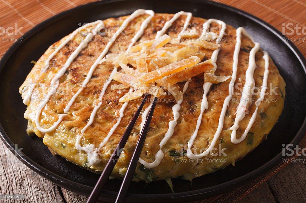 Japanese fast food: okonomiyaki close-up and chopsticks. horizontal stock photo