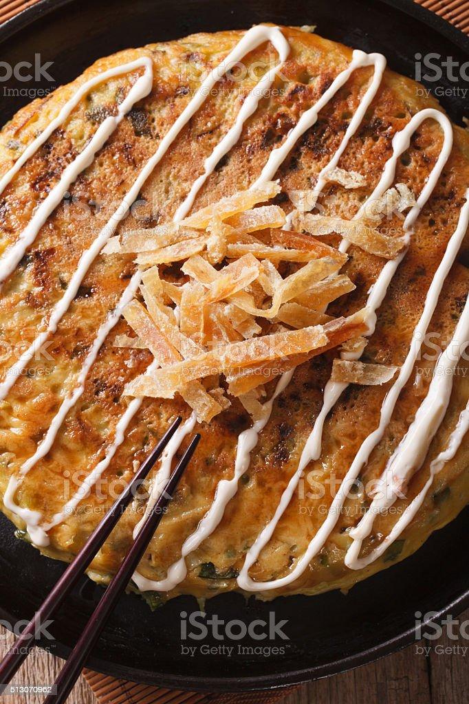 Japanese fast food: okonomiyaki close-up and chopsticks. Vertical stock photo