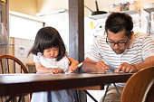 istock Japanese Father and Daughter Filling out Paperwork on Kitchen Table 539021036