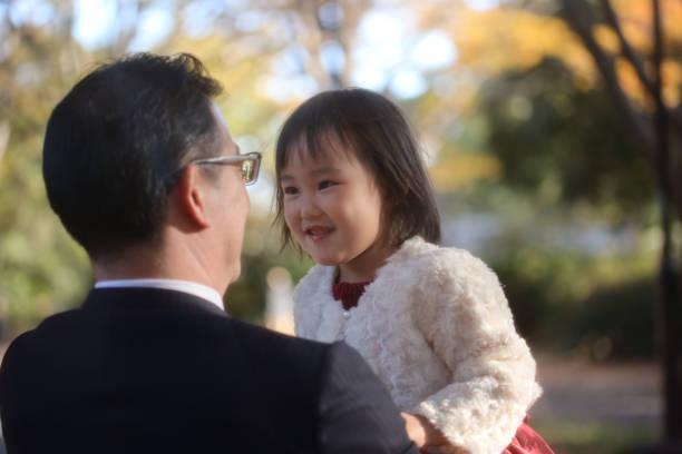 日本父親抱著女兒在石池去三慶典圖像檔
