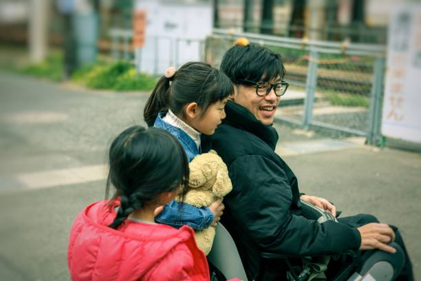 Japanese father on the wheelchair and Daughter Japanese family is having fun at the park als stock pictures, royalty-free photos & images