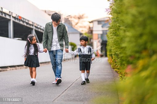 Single Japanese father holding hands with his elementary age son and daughter as he walks them home from school.