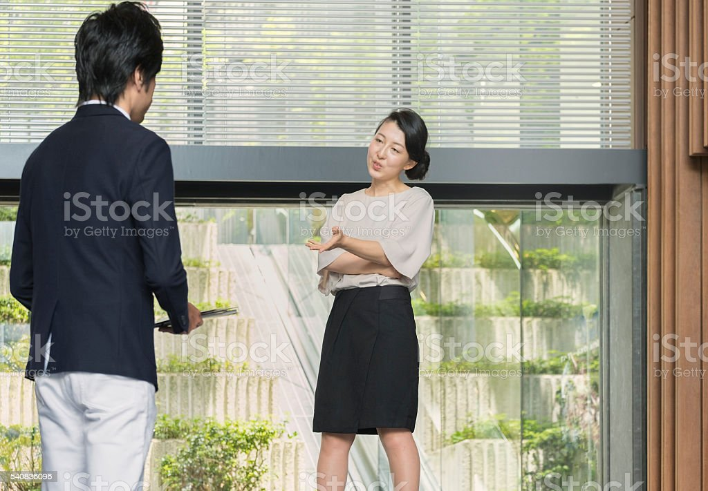 Japanese Female Boss Speaking to Male Employee in Office Lobby stock photo
