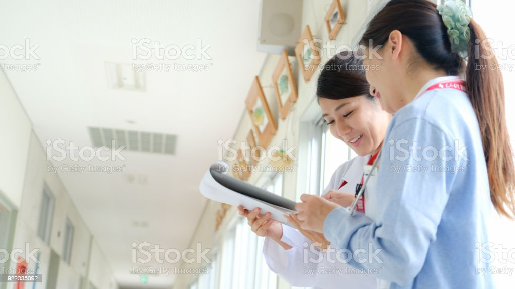 A Japanese female doctor and a nurse. Meeting while looking at the chart in the hallway. stock photo