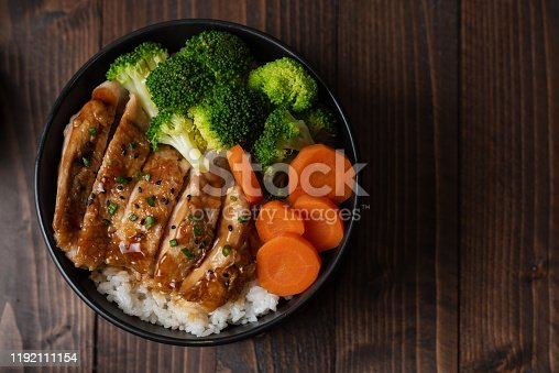 Japanese Food Style : Top view of Homemade Chicken Teriyaki grilled with rice , carrot , broccoli put on the black bowl and place on wooden table