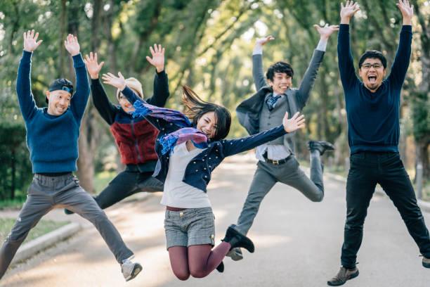 日本人の友達が一緒にジャンプ ストックフォト
