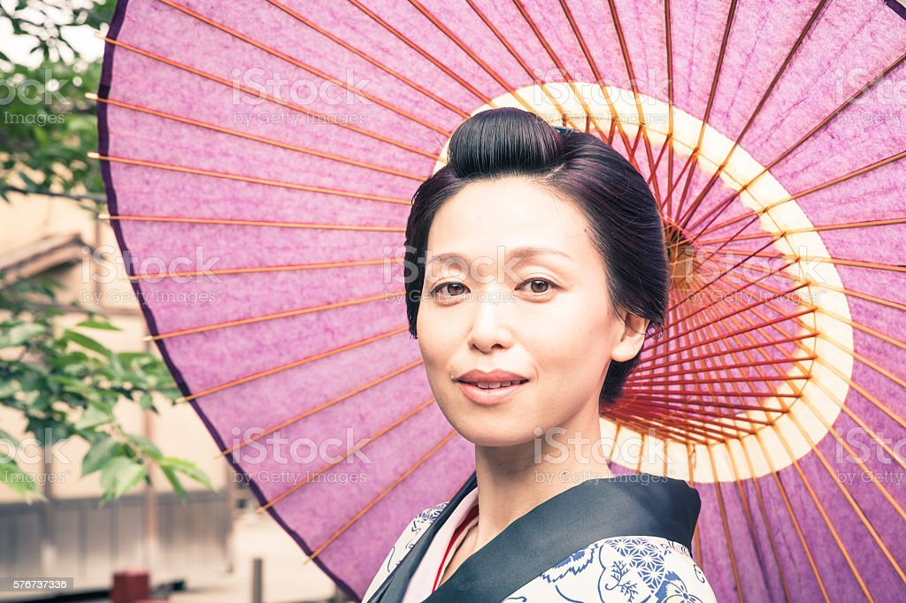 Japanese geisha  with paper umbrella in historic Kyoto stock photo