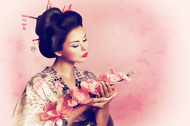 Japanese geisha woman Portrait of a Japanese geisha woman with flower geisha stock pictures, royalty-free photos & images