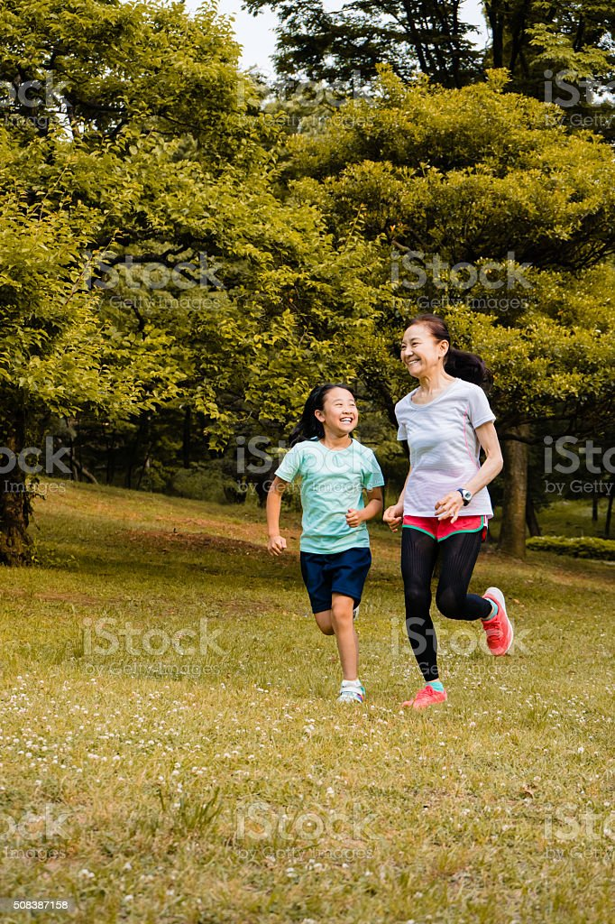 Japanese girl and grandmother running in the park stock photo