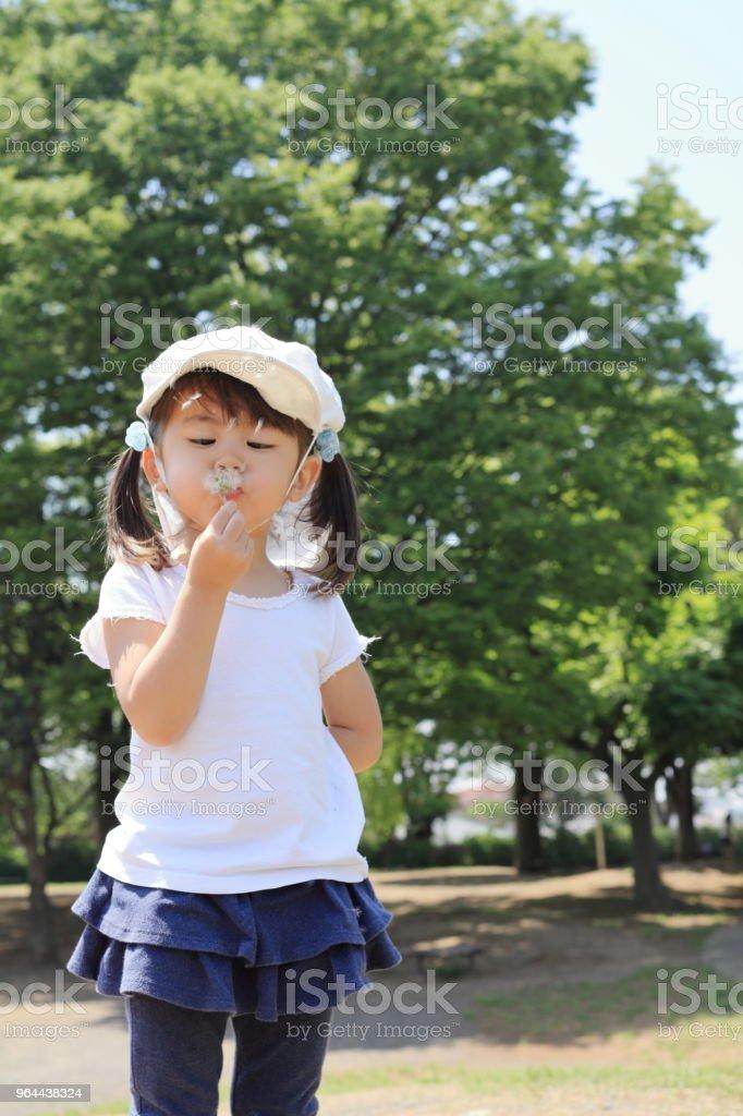 Japans meisje waait paardebloem zaden onder de blauwe hemel (3 jaar) - Royalty-free 2-3 jaar Stockfoto