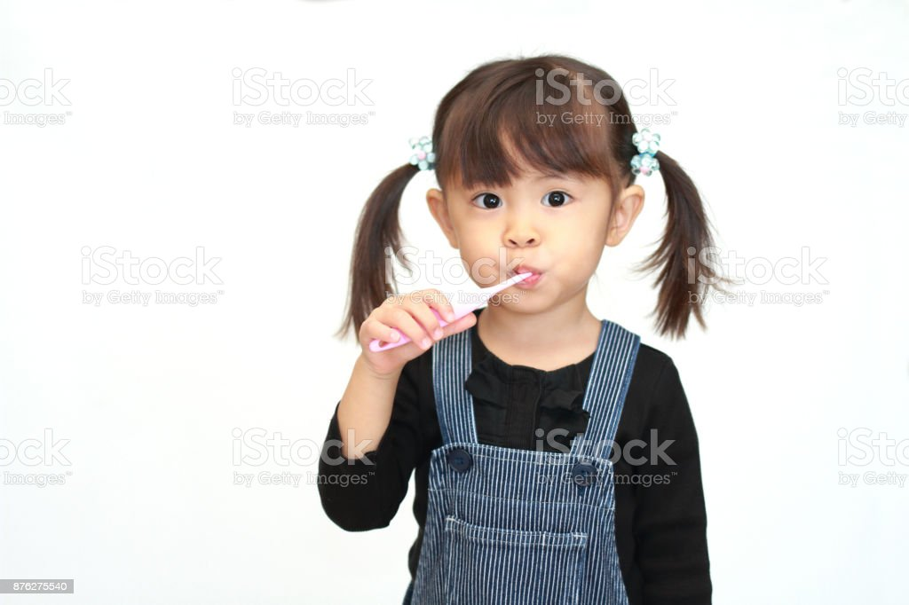 Japanese girl brushing her teeth (3 years old) stock photo