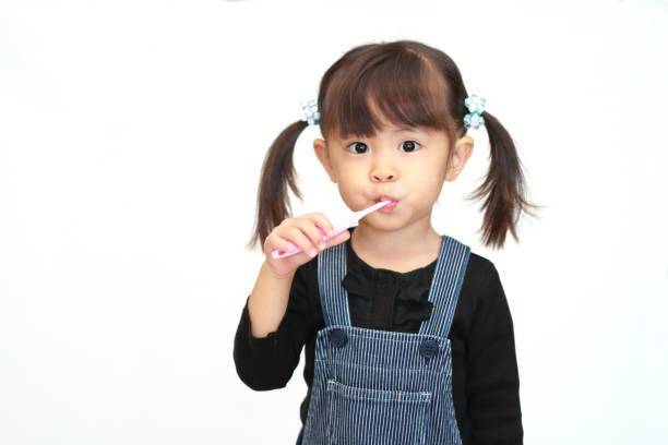 Japanese girl brushing her teeth (3 years old) stock photo