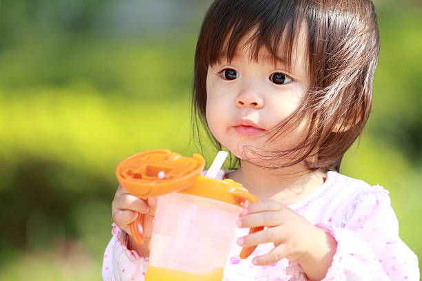 Japanese girl drinking water (1 year old) stock photo