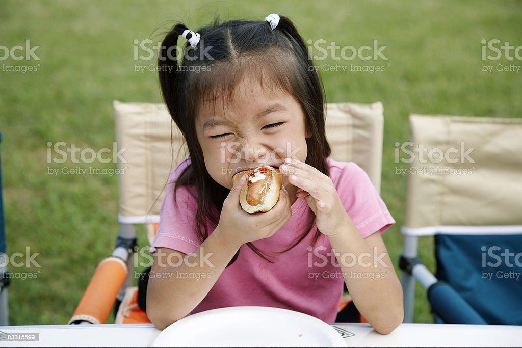 Japanese girl eating a hot dog royaltyfri bildbanksbilder