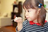 日本の女の子 (3 歳) の誕生日ケーキを食べる