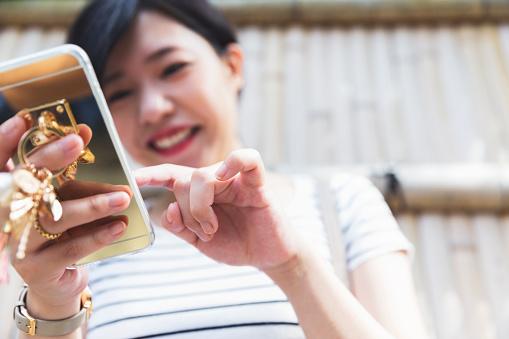 Japanese girl exploring social media feed on her smart phone
