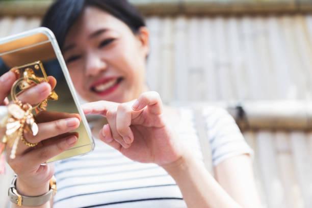 Japanese girl exploring social media feed on her smart phone stock photo