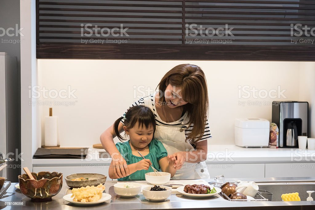 Japanese girl helping mother in the kitchen stock photo