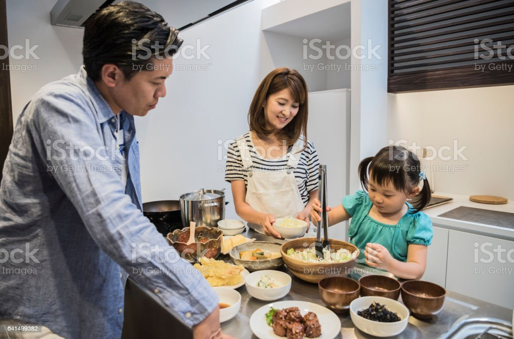 Japanese girl helping parents in kitchen stock photo