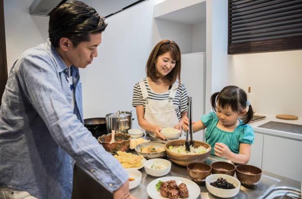 キッチンで両親を助ける日本の女の子 ストックフォト