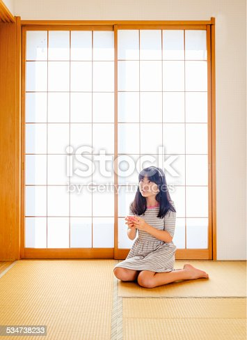 A Japanese girl holds a cellphone while kneeling on tatami flooring in front of a shoji window in her home.