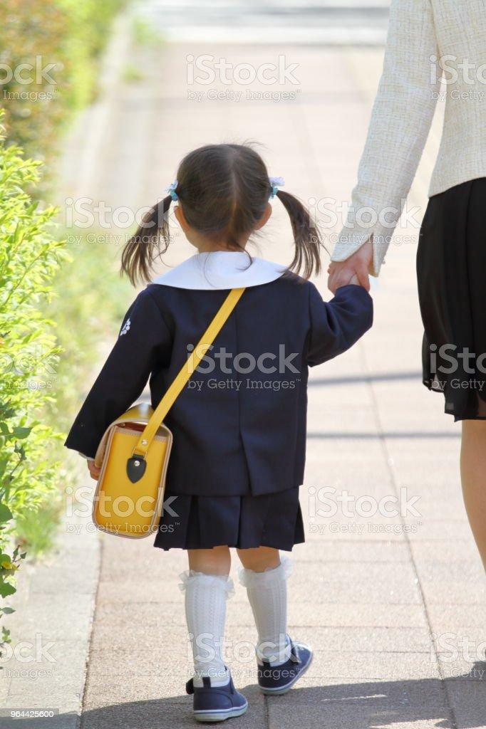 Japans meisje in uniform van de kleuterschool omklemde haar moeder's hand (3 jaar oud) (terugtrekkende figuur) - Royalty-free 2-3 jaar Stockfoto